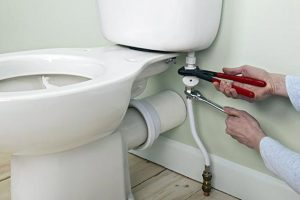 man fixing toilet
